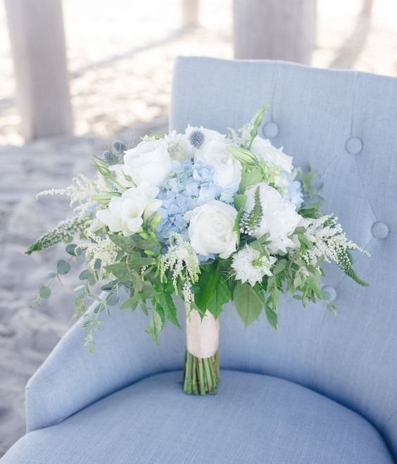 a nautical wedding bouquet of white roses, blue hydrangeas, thistles, astilbe and greenery is a beautiful idea
