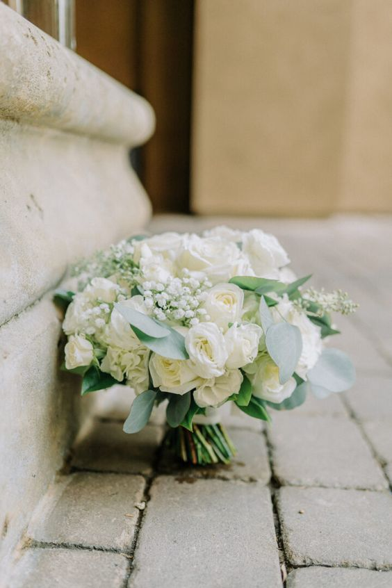 an elegant white rose and baby's breath wedding bouquet with greenery is a chic idea for a nautical wedding