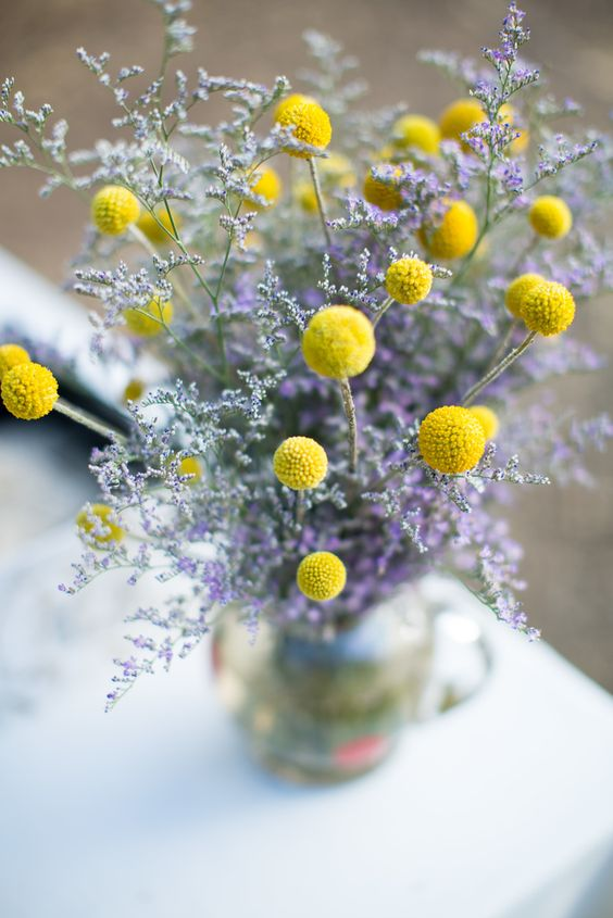 a beautiful billy balls and lavender wedding centerpiece in a silver vase is a stylish idea for a vintage wedding