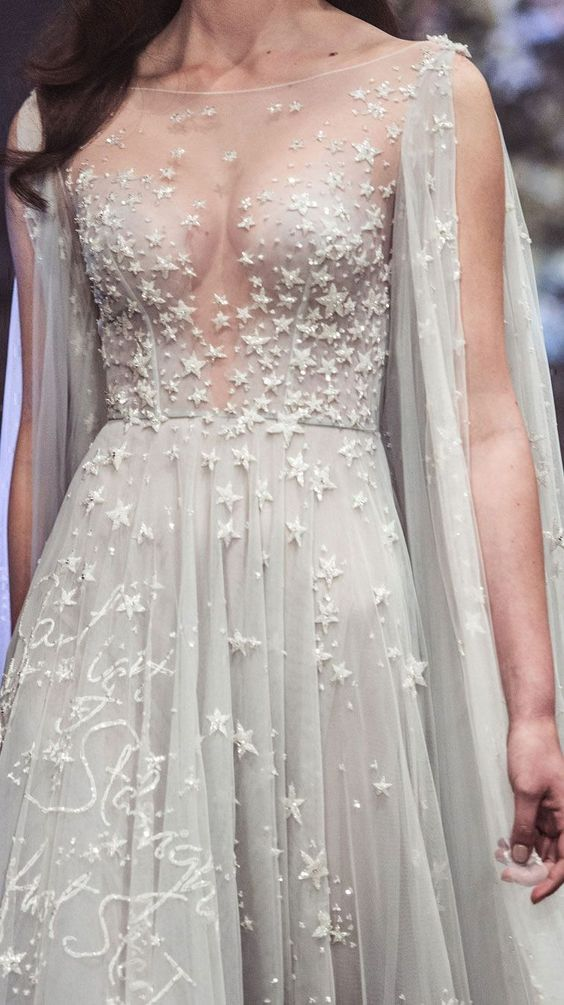 a beautiful grey A line wedding dress with an illusion high neckline, long cut sleeves and sparkling stars all over the dress