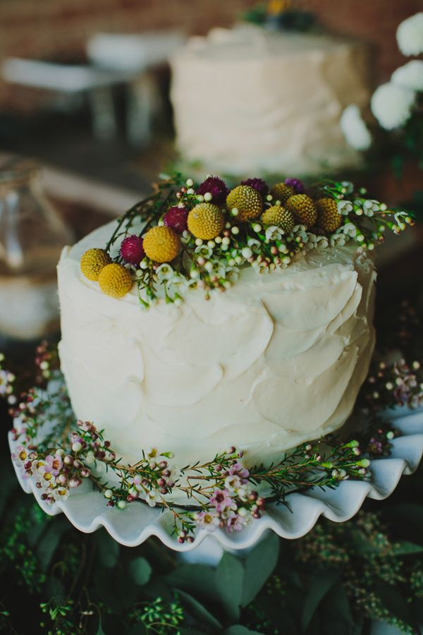 a beautiful summer wedding cake topped with billy balls, waxflowers and some bright allium is ideal for a wildflower wedding