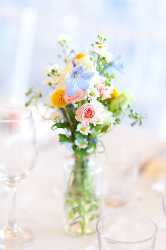 a beautiful summer wedding centerpiece of greenery, blue and pink blooms and billy balls is a lovely idea for a brigth wedding