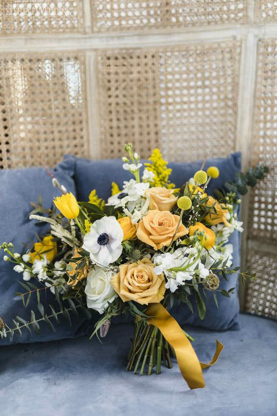 a beautiful wedding bouquet with yellow and white roses, white anemones, billy balls, eucalyptus and yellow tulips for spring or summer