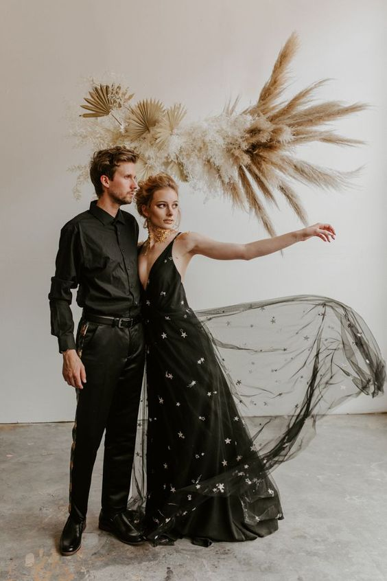 a black A-line wedding dress with a plunging neckline, straps and silver stars all over the gown is a bold and statement idea to try