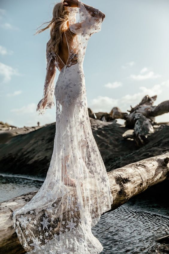a boho celestial mermaid wedding dress with a cutout back, bell sleeves, a train and white embroidered stars all over the gown