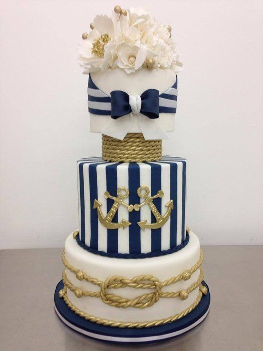 a bold and refined nautical wedding cake with white, navy and white striped tiers, gold ropes, gold anchors, white sugar blooms and pearls