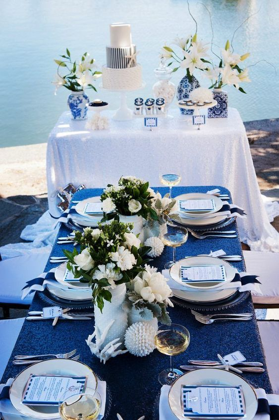 a bold nautical glam wedding tablescape with a navy sequin tablecloth, white florals, seashells and corals and white plates