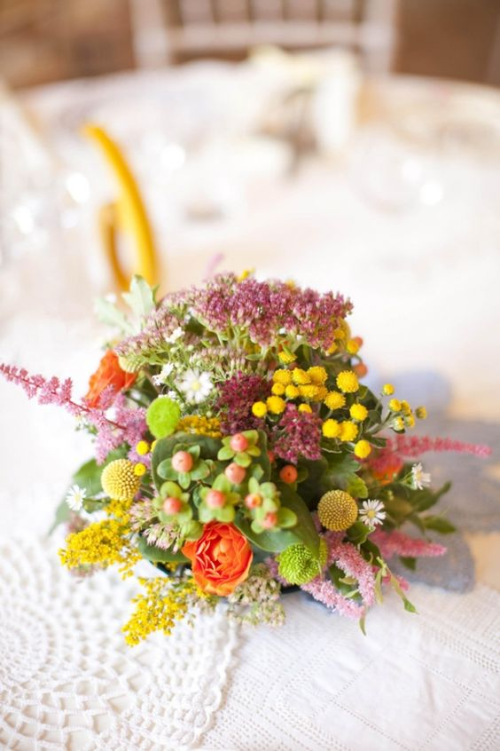 a bright and colorful wedding centerpiece of pink and yellow blooms, berries, billy balls and greenery for summer