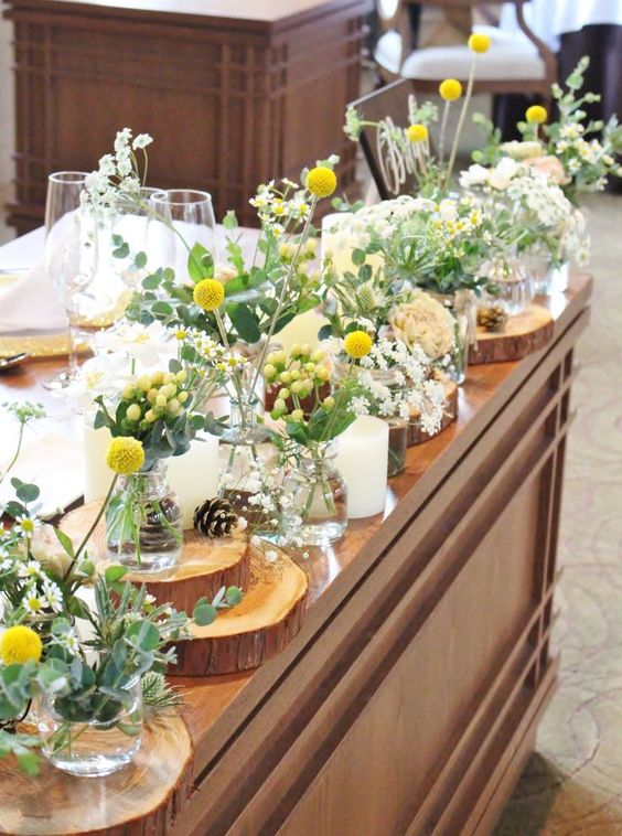 a bright and cool cluster wedding centerpiece of yellow berries and billy balls, white blooms and greenery, candles and pinecones