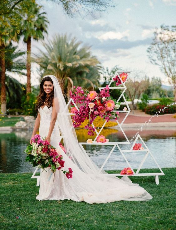 a bright and cool geometric wedding backdrop of white triangles decorated with super bold blooms is a lovely idea for a mid-century modern wedding
