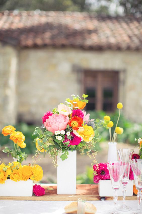a bright cluster wedding centerpiece of hot pink and pink blooms plus yellow ones, billy balls and greenery for a bright summer wedding