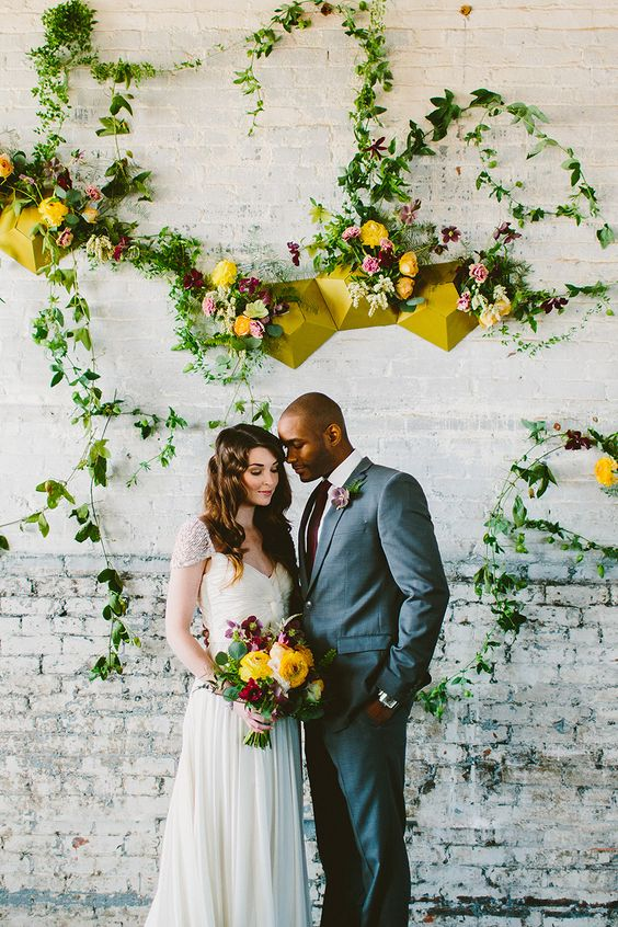 a bright mid-century modern wedding backdrop - a brick wall, mustard geometric decor, greenery and colroful blooms is a lovely idea