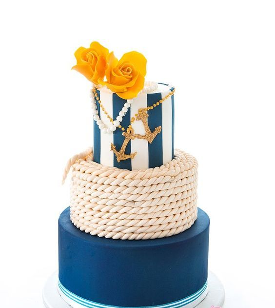 a bright nautical wedding cake with a rope, a navy and a striped tier, gold glitter anchors, pearls and yellow roses is a bold and cool idea