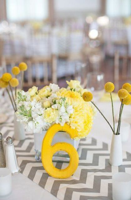 a bright spring or summer wedding centerpiece with a chevron runner, a yellow table number, bright yellow and white blooms, billy balls in vases