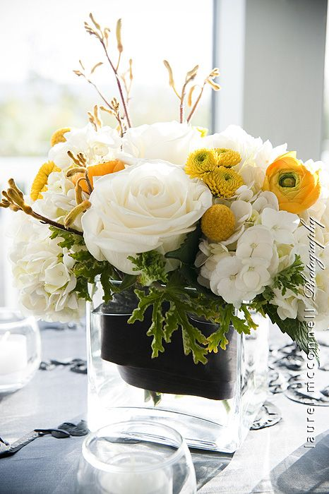 a bright summer wedding centerpiece of a clear vase, greenery, white and yellow blooms and billy balls