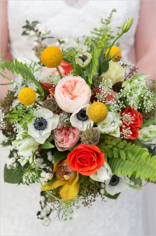 a bright wedding bouquet of pink peonies, white anemones, coral roses, lots of greenery and billy balls
