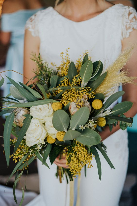 a bright wedding bouquet with foliage, white roses, mimosa, billy balls and some grass for a bold summer wedding