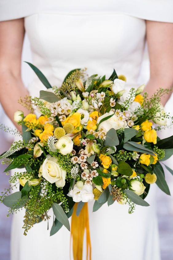 a bright wedding bouquet with greenery, white and yellow blooms, billy balls, astilbe and yellow ribbons is amazing