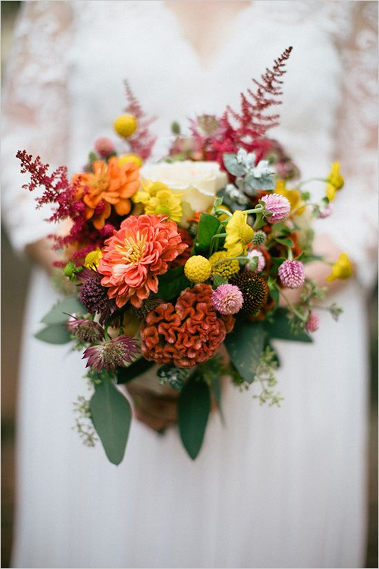 a bright wedding bouquet with orange, white, pink blooms, dark foliage and billy balls for a fall wedding