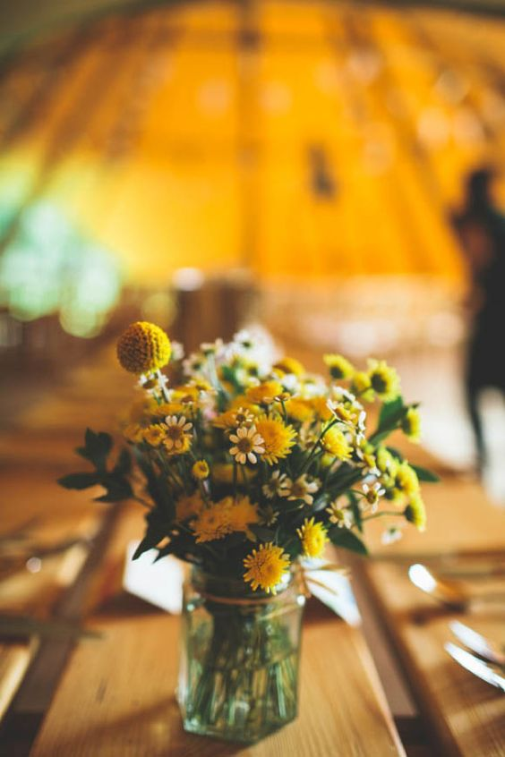 a bright wedding centerpiece of greenery, white and yellow blooms and billy balls is a simple idea for spring or summer