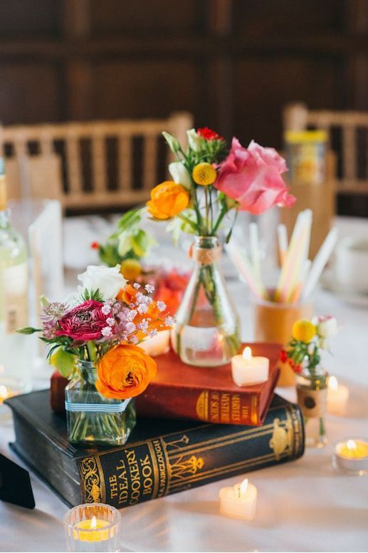 a bright wedding centerpiece of stacked books and candles, bright blooms and billy balls for a colorful summer wedding