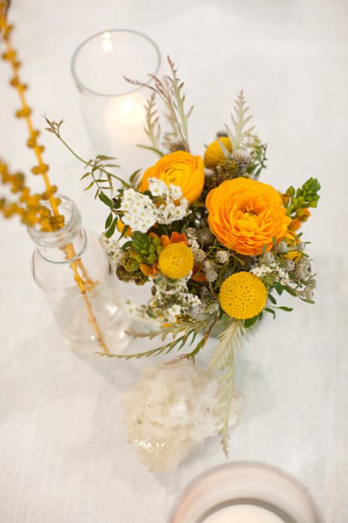a bright wedding centerpiece of yellow and white blooms, berries and greenery is a pretty idea for a summer or fall wedding
