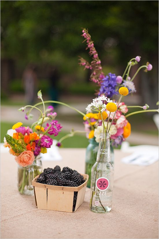 a bright wildflower wedding centerpiece of various colorful wildflowers and billy balls plus some fresh berries is lovely