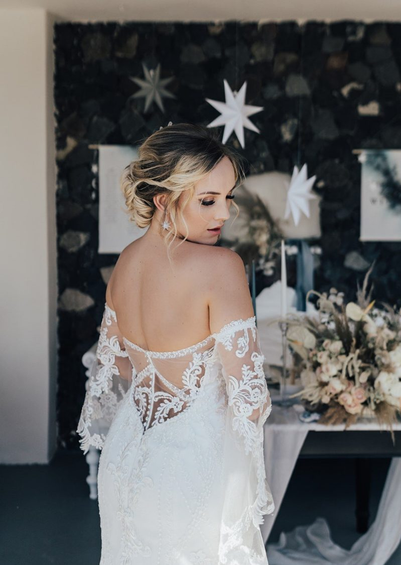 a chic fitting wedding dress with an off the shoulder neckline, a lace covered back and bell sleeves plus an illusion back just wows