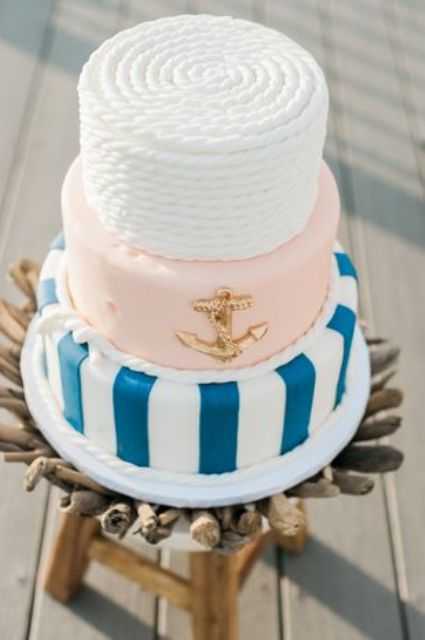 a chic nautical wedding cake with a white rope, blush, navy stripe tier plus a gold anchor is a gorgeous idea to rock