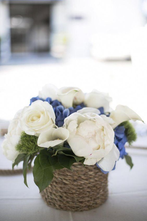 a chic nautical wedding centerpiece of white and blue blooms and foliage in a vase wrapped with rope