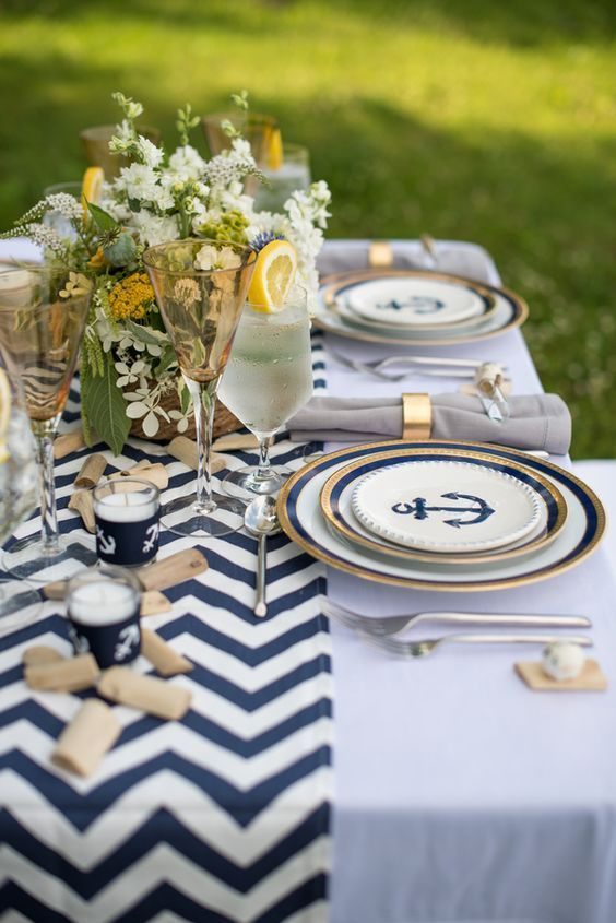 a chic nautical wedding tablescape with a chevron table runner, driftwood, neutral blooms and greenery, nautical plates and candles