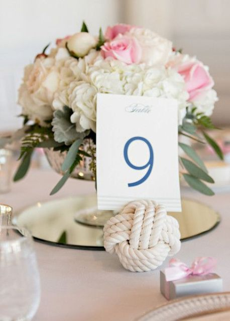 a chic wedding centerpiece with white and pink blooms in a refined bowl, a rope knot with a table number is classics
