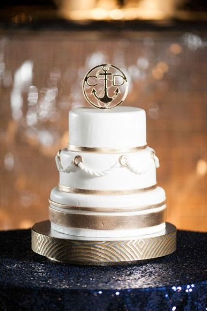 a chic white and gold wedding cake with stripes, ropes and a gold cake topper is a gorgeous idea for a modern seaside wedding