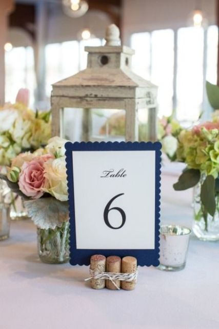 a classic nautical wedding centerpiece of a shabby chic candle lantern, white and pink blooms and greenery, a navy table number