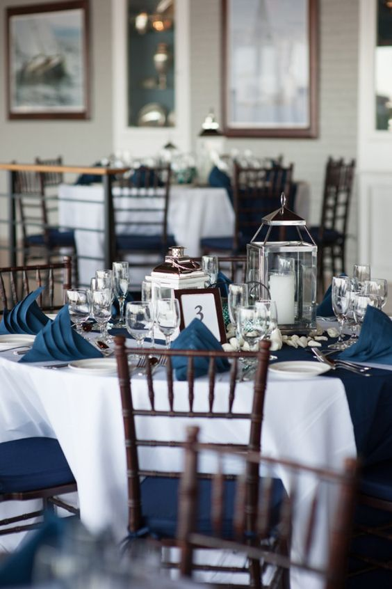 a classic nautical wedding tablescape with a white tablecloth, navy napkins, white pebbles and candles in oversized candle lanterns