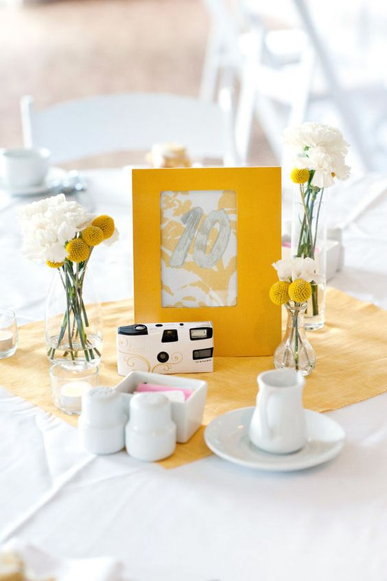 a cluster wedding centerpiece of clear vases, white blooms and billy balls plus a table number and a camera