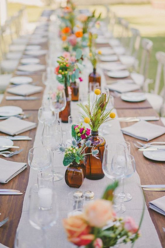 a colorful cluster wedding centerpiece of thistles, bold blooms and greenery and billy balls plus a burlap table runner