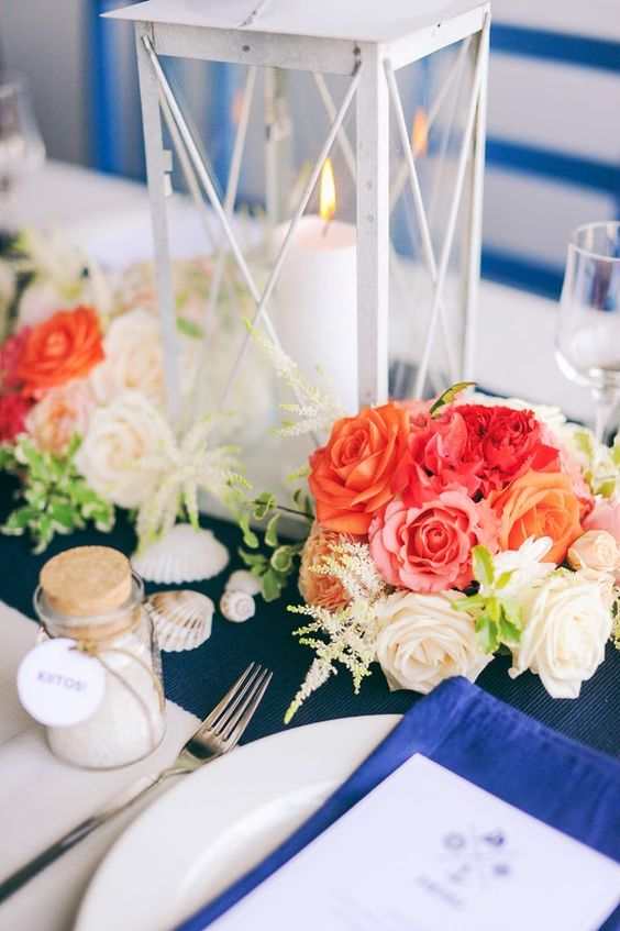 a colorful nautical wedding table setting with a navy table runner, a bold blue napkin, colorful blooms and a candle lantern, shells and sand in a jar