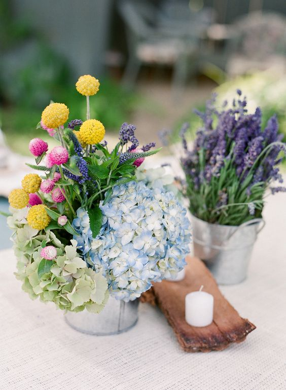 a colorful rustic cluster wedding centerpiece of buckets with hydrangeas, billy balls and lavender plus a wooden piece with a candle