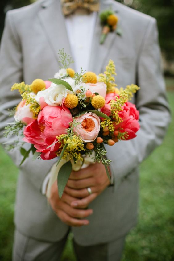 a colorful wedding bouquet with coral and blush peonies, white roses, billy balls and mimosa is very bright and cool