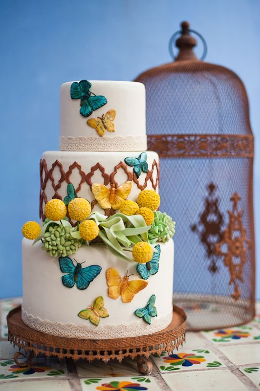 a colorful wedding cake with Moroccan patterns, bright butterflies, grreenery and billy balls plus lace ribbon is chic and bold
