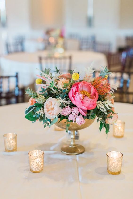 a colorful wedding centerpiece of a brass bowl, bold pink and blush blooms, greenery and billy balls for spring or summer
