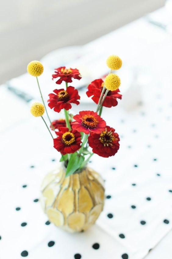 a colorful wedding centerpiece of bold red blooms and billy balls plus a catchy yellow vase for a summer or fall wedding
