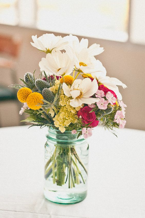 a colorful wedding centerpiece of white, pink, green, hot pink blooms, thistles and billy balls for a summer wedding