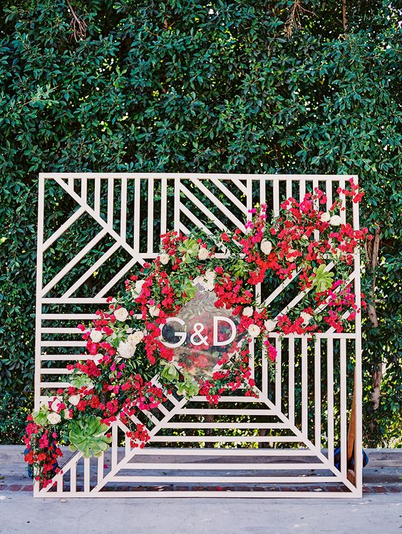 a cool mid-century modern wedding backdrop of plywood decorated with monograms, greenery, white and hot red blooms is very chic