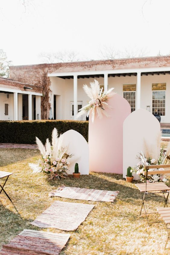a cool mid-century modern wedding backdrop of white and pink parts, pampas gras and neutral blooms and potted cacti is a chic idea