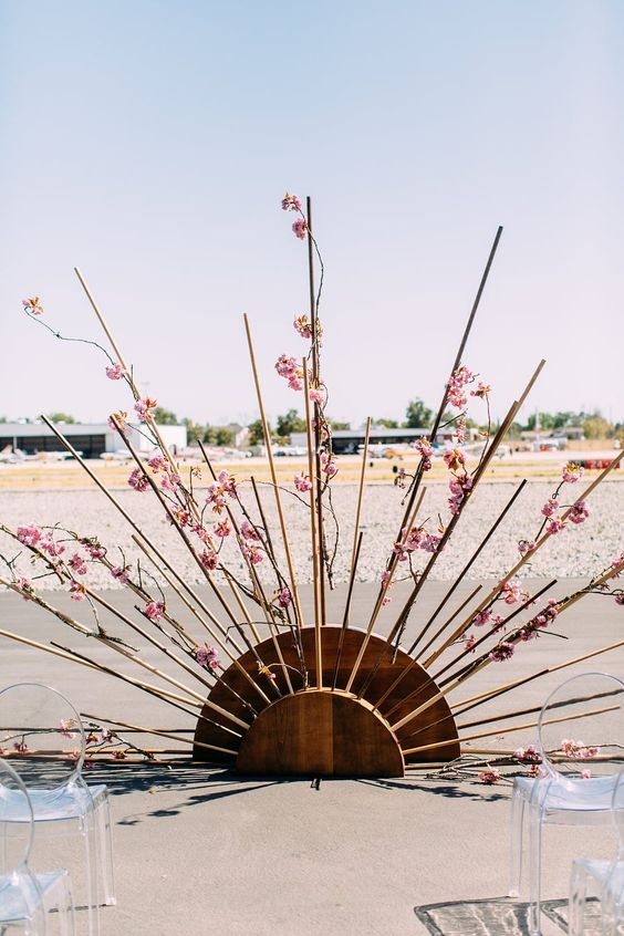 a cool sunburst wedding altar decorated with pink blooms and acrylic chairs for a mid-century modern wedding