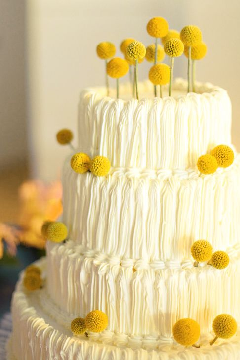 a cool white buttercream wedding cake decorated with billy balls is a lovely idea for spring or summer