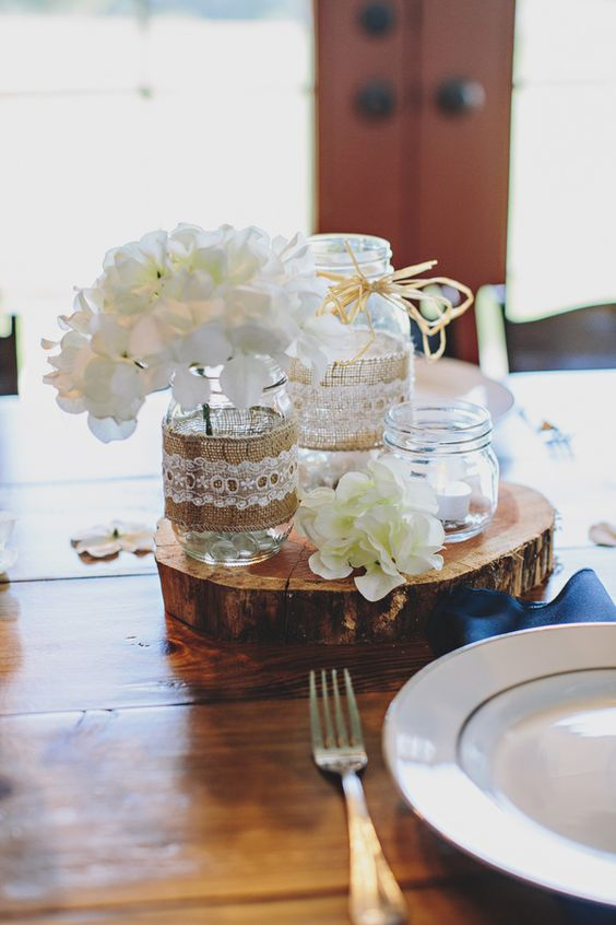 a country nautical wedding centerpiece of a wood slice, white blooms, jars with candles and blooms is amazing and always in trend