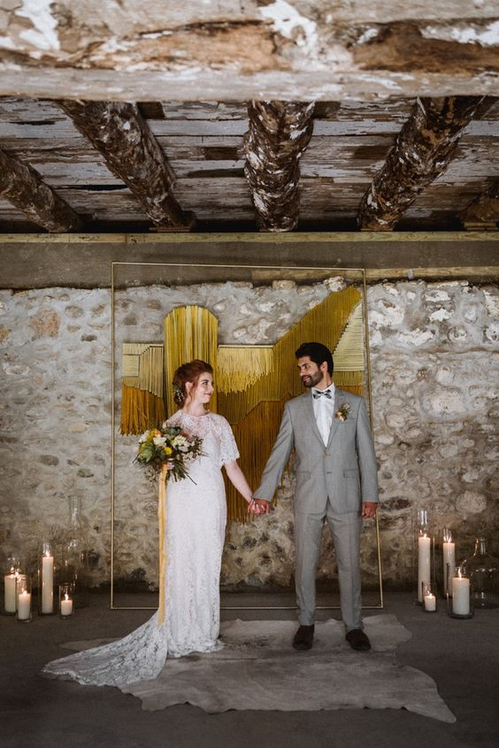 a creative mid-century modern wedding backdrop of godl and mustard yarn, candles on the floor and a rug is a cool and bold idea